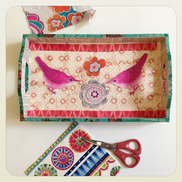 wooden serving tray decoupaged with an assortment of papers applied in layers